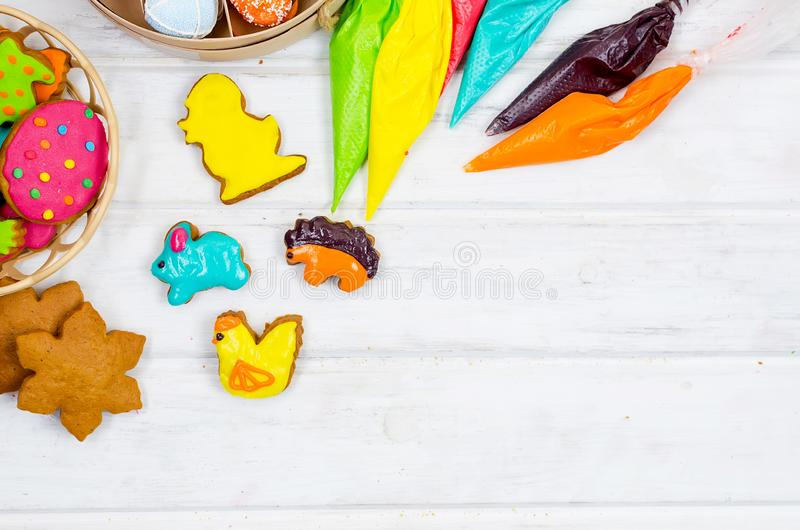 Girl decorating gingerbread with icing for Easter. Child hands decorating honemade gingerbread with icing sugar using a pipping bag. Easter Treats. Handmade royalty free stock images