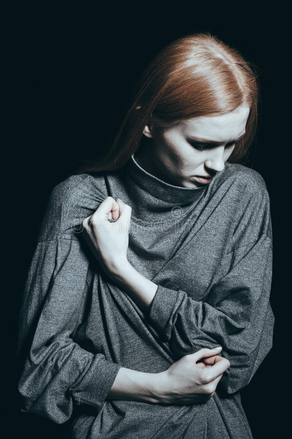 Girl deep in thought. Depressed girl deep in thought holding her fist to her chest in a concept of abuse stock images