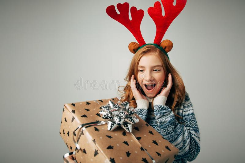 Girl with deer horns in a sweater smiles. She is shocked by such a great gift. Parents pleasantly surprised the teenager stock photos