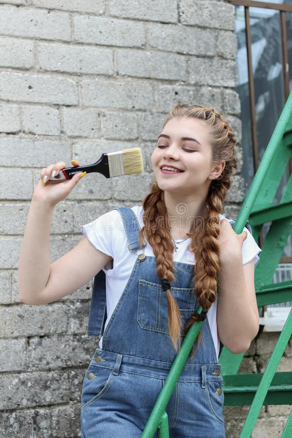 The girl makes preparing for painting a wooden surface gazebo, fence stock photos