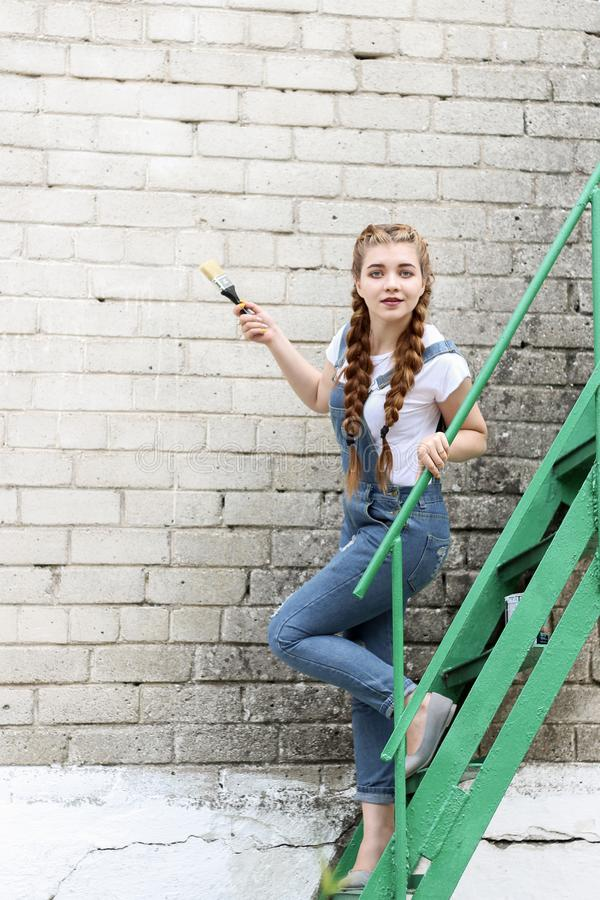 The girl makes preparing for painting a wooden surface gazebo, fence royalty free stock photos