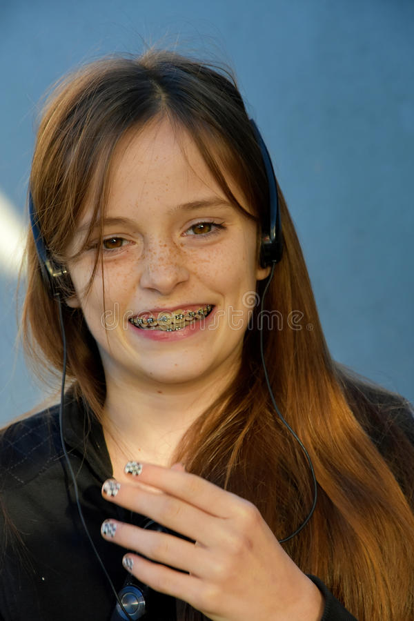 Girl with dental braces. Happy teenage girl with dental braces and headphones stock image