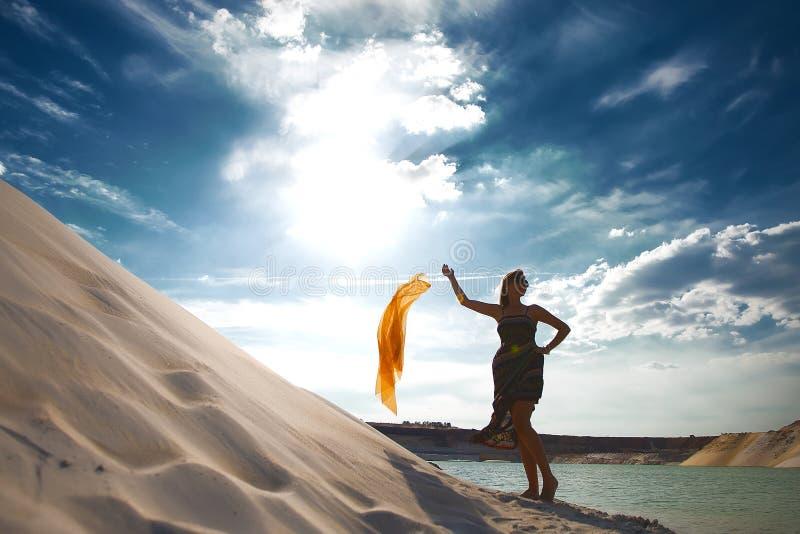 Girl in desert near oasis royalty free stock image