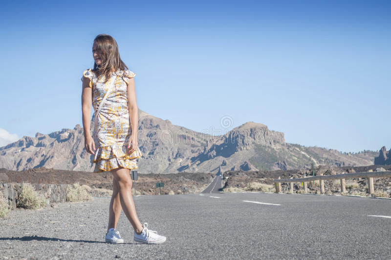Girl on a deserted road. In the mountains stock images