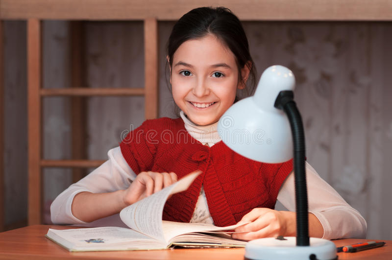 Girl at desk reading a book by light of the lamp royalty free stock images