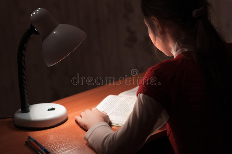 Girl at desk reading a book by light of the lamp royalty free stock photography