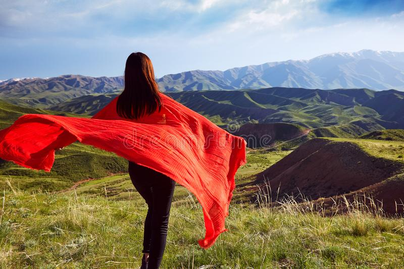 Girl with a developing cape on the background of the spring mountain landscape royalty free stock image