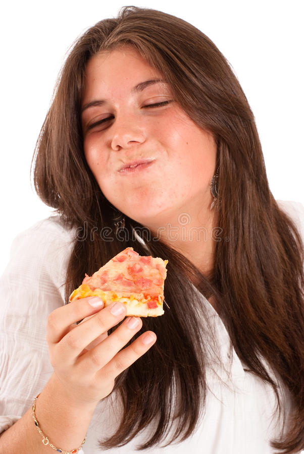 Girl devouring a pizza. Isolated image of a young girl eating a piece of pizza with relish stock photo