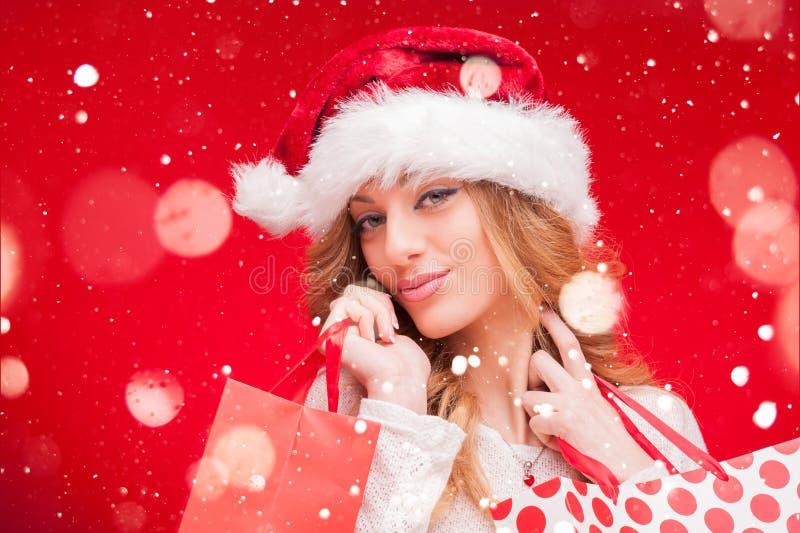 Girl di modello biondo in Santa Hat sopra rosso fotografia stock