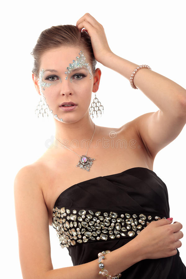 Girl with diamonds. Girl looking straight in the camera with diamond make-up, pink neck lace, pearl bracelet and silver earrings on a white background. She wears royalty free stock photos