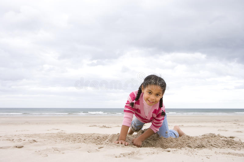 Girl (5-7) digging hole on beach, smiling, portrait royalty free stock images