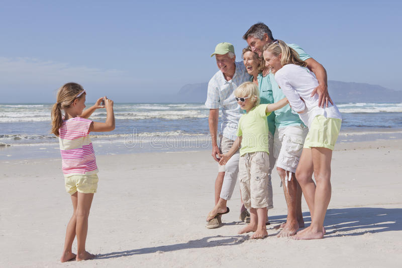 Girl with digital camera photographing multi-generation family on sunny beach stock images
