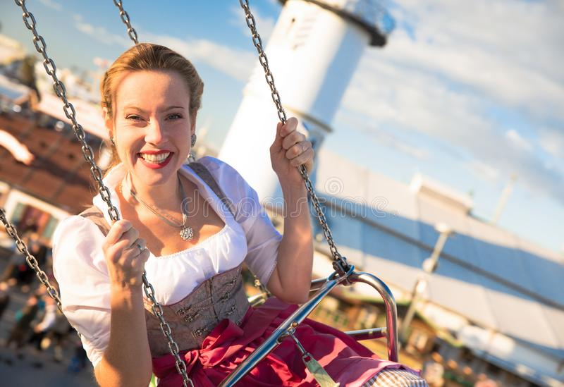 Girl with dirndl does oktoberfest wiesn in munic. Young woman is doing oktoberfest in munic bavaria in the spring summer autumn folk festival. she is wearing a stock photos