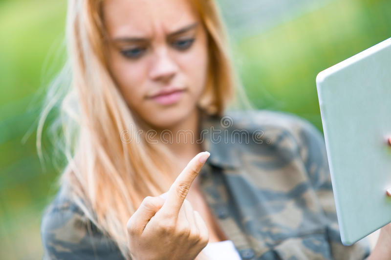 Girl disgusted by something on her finger. Girl outdoors with a tablet discovers something disgusting on her finger and looks at that disappointed royalty free stock images
