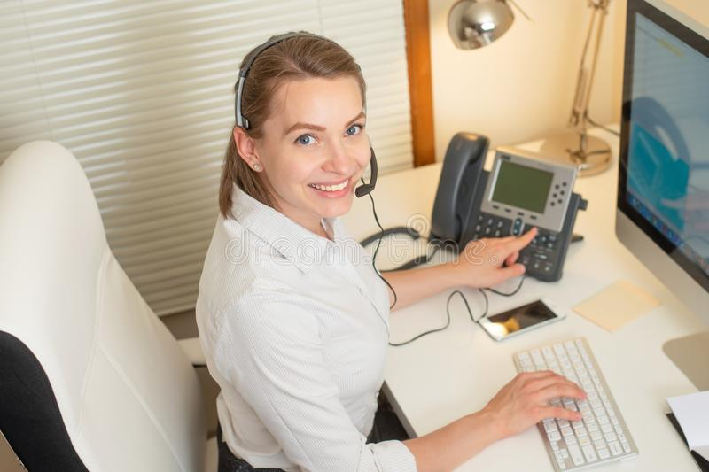 Girl dispatcher works with the phone. In the call center royalty free stock photos
