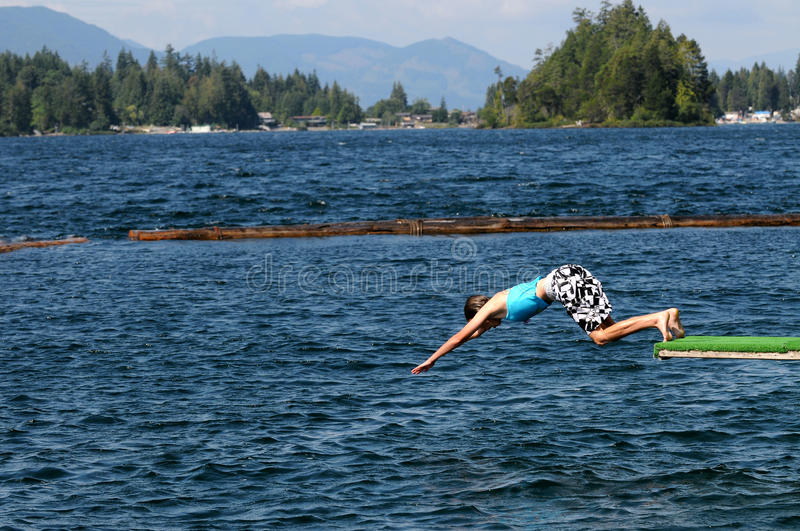 Girl diving into lake stock photography