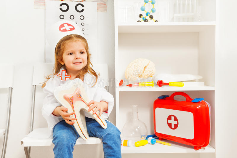Girl in doctor costume with cap holds tooth model. Little smiling girl in doctor costume with cap holds tooth model at the medical room stock images