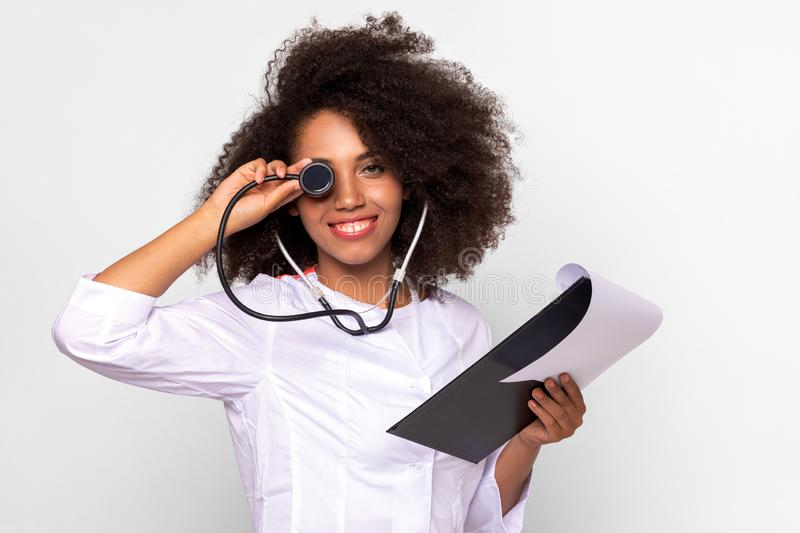 Girl doctor jokes playing with stethoscope. Girl doctor smiles and jokes playing with stethoscope. girl doctor with lush curly hair, in a medic uniform on a stock photo