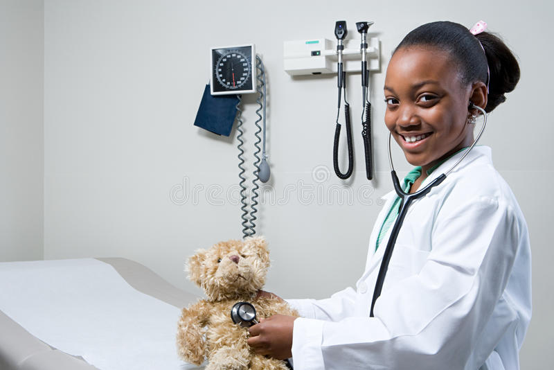 Girl doctor using stethoscope on teddy bear royalty free stock images