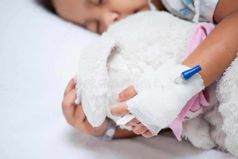 Girl& doente x27 da criança; mão de s com intravenous salino & x28; iv& x29; gotejamento imagens de stock