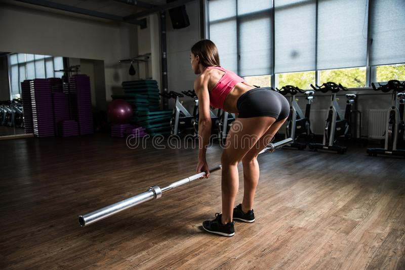 Girl does a deadlift with a blank recordable rod in the hall of fitness. royalty free stock image