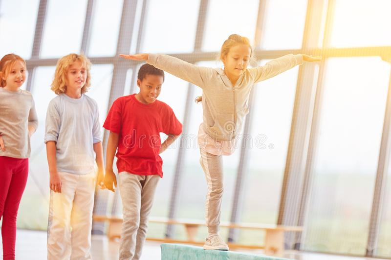 Girl does gymnastics in gym class stock image
