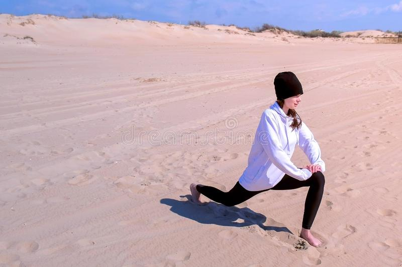Girl does High Lunch Pose on sea sand beach yoga training sport exercise outdoor. Young girl does High Lunch Pose on sea sand beach. She is beginner in yoga royalty free stock image