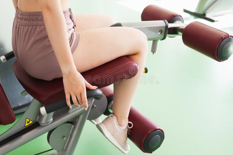 Girl does a leg extension exercising. In a gym royalty free stock images