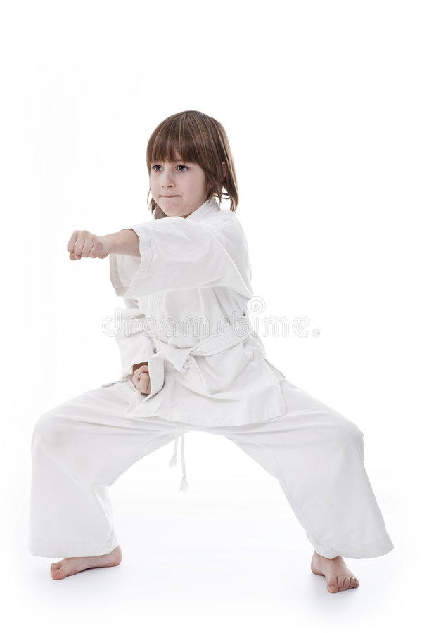 Girl does taekwondo. Little girl having taekwondo classes royalty free stock photography