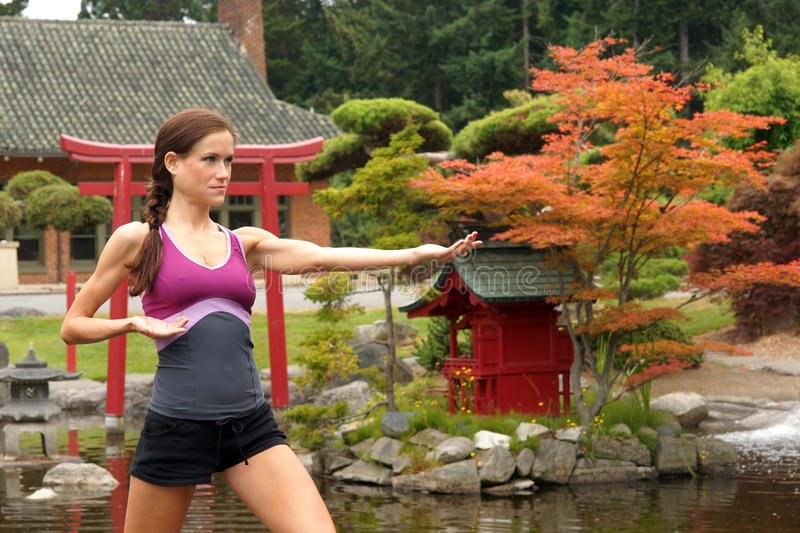 Girl does Tai Chi Standing Pagoda Japenese Garden royalty free stock image