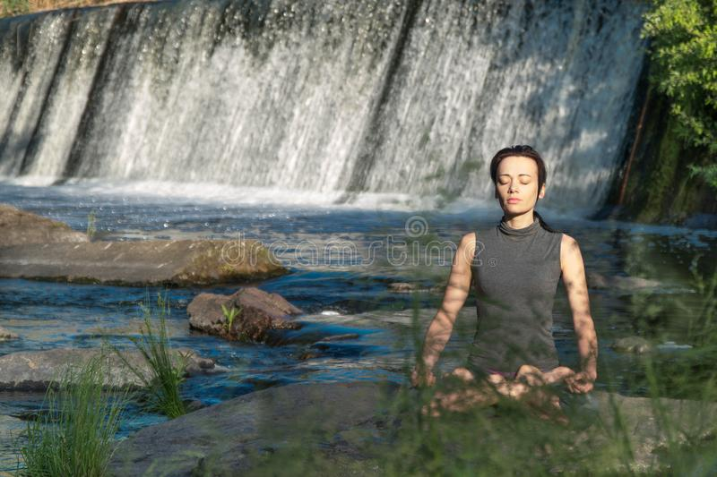 Girl does yoga in the background of a waterfall.  stock photography