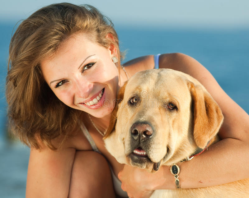 Girl with dog. Young woman with Labrador male dog on the coast of the sea royalty free stock photos