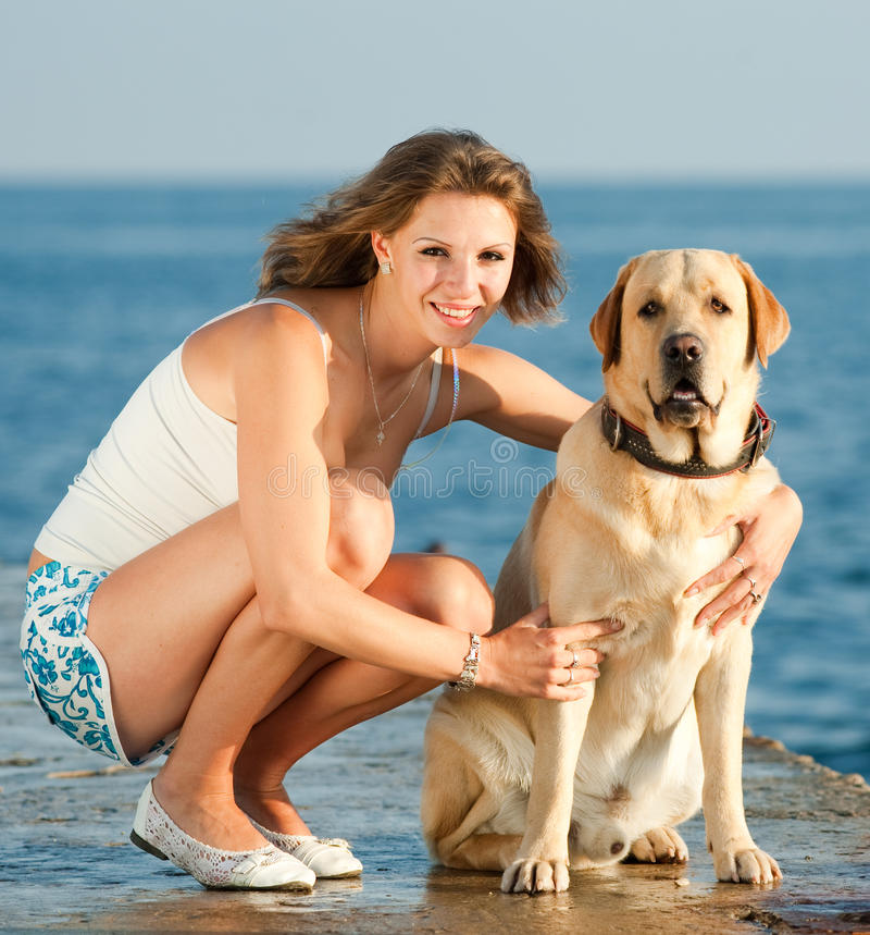 Girl with dog. Young woman with Labrador male dog on the coast of the sea stock photos