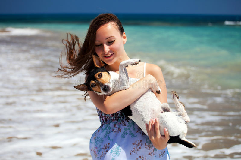 Girl and the dog. A young girl resting with her dog in the beach