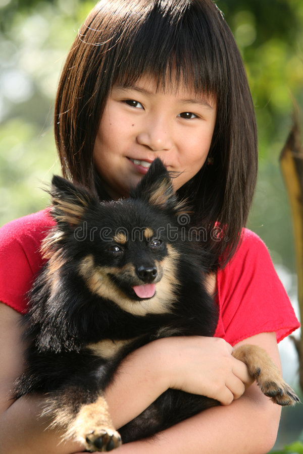 Girl with a Dog. Happy 9 years old Chinese girl with her dog royalty free stock images