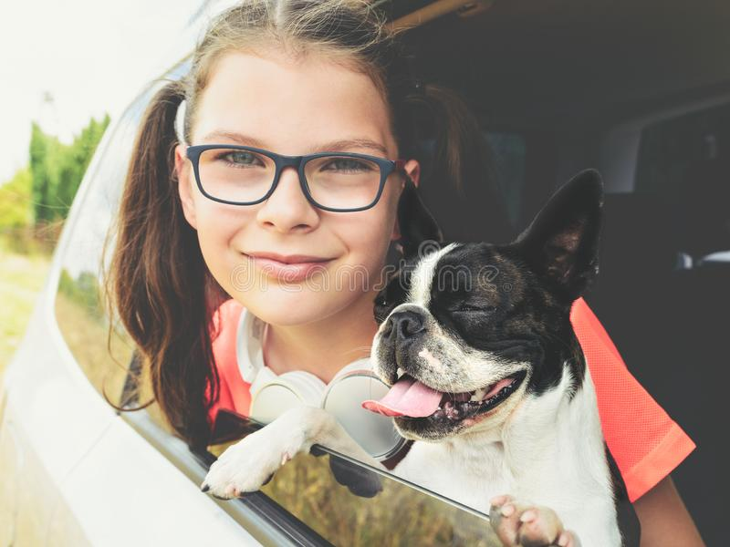 Girl and dog - boston terrier - looking out the open car window - friendship concept royalty free stock images