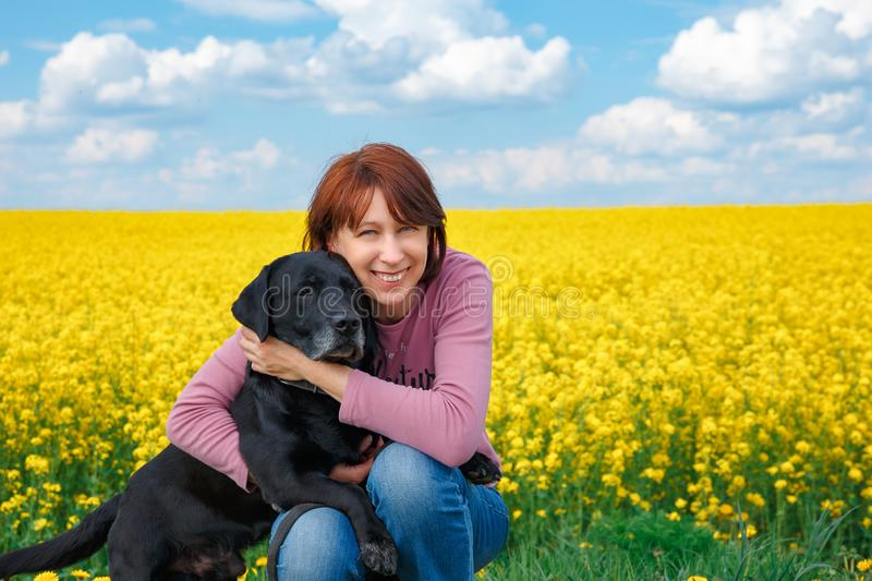 Girl with a dog on the field of yellow flowering rape royalty free stock photo