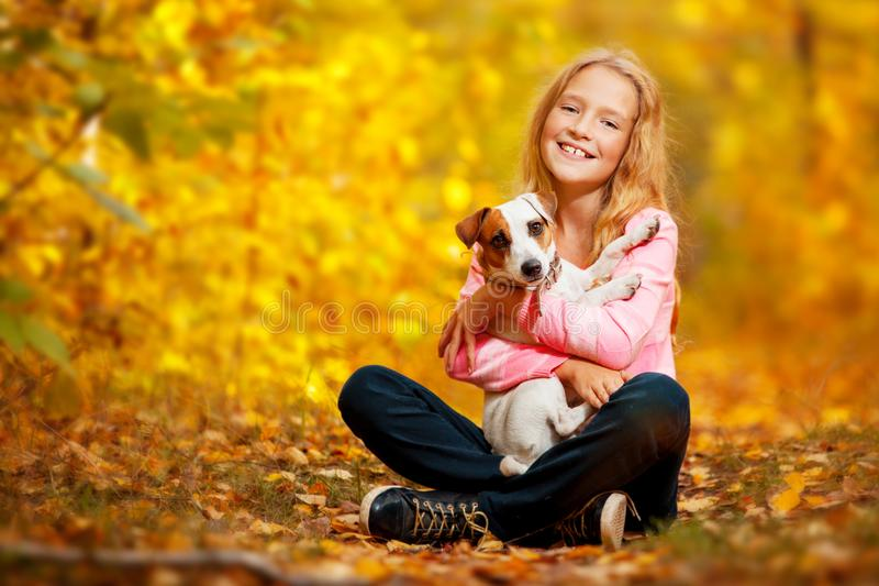 Happy girl with dog at autumn. Girl with dog outdoors. Child with pet at autumn stock images