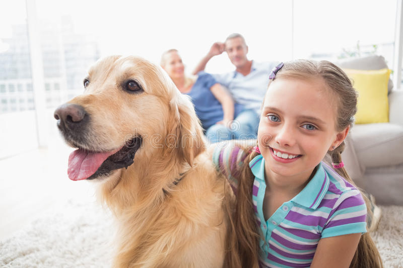 Girl with dog while parents relaxing at home. Portrait of happy girl with dog while parents relaxing in background at home royalty free stock photos