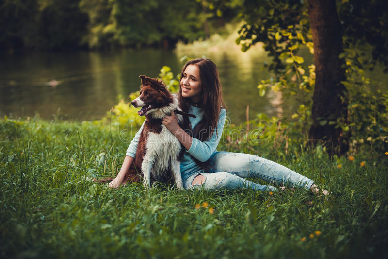 Girl and dog sitting on the grass stock photos