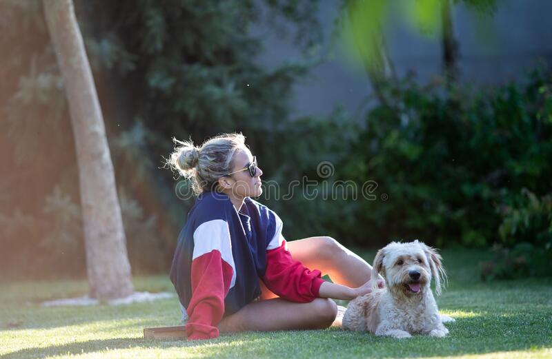 Girl with dog sitting on grass in park royalty free stock images