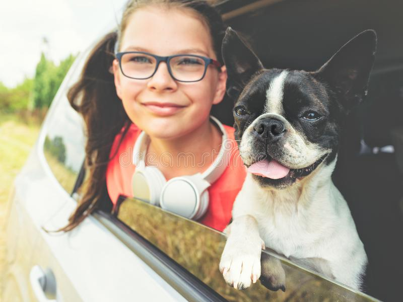 Girl and dog - terrier - looking out the open car window - friendship concept royalty free stock photography