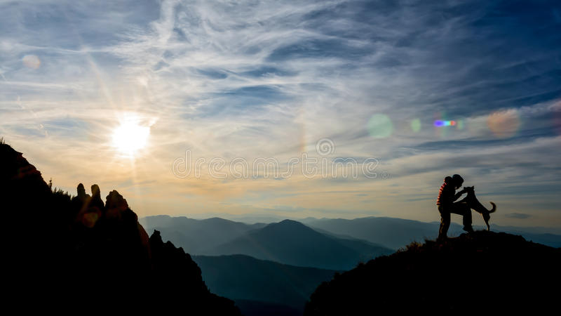 Girl and dog on top of the mountain. Girl training her dog on top of the mountain royalty free stock photo