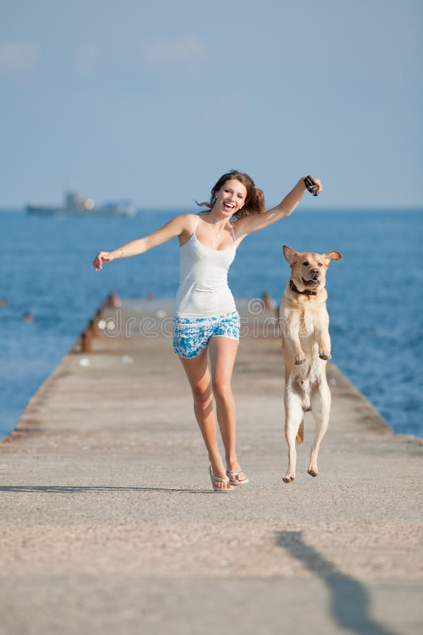 Girl with dogs. Young woman with Labrador male dog running along the pier stock photo