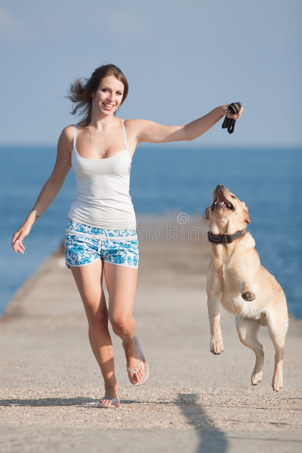 Girl with dogs. Young woman with Labrador male dog running along the pier stock photos