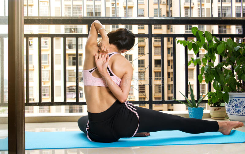 Girl doing Cow face yoga pose modification. At home royalty free stock photos