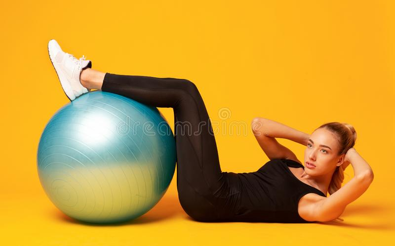 Girl Doing Curl Up With Legs On Fitball In Studio stock photo
