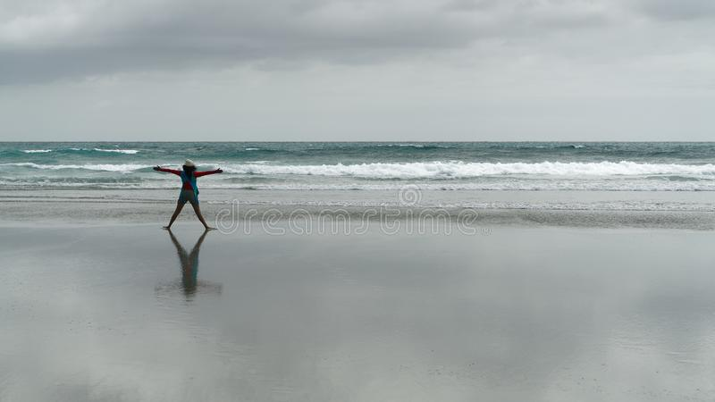 Girl doing exercises on an empty beach, New Zealand royalty free stock photography