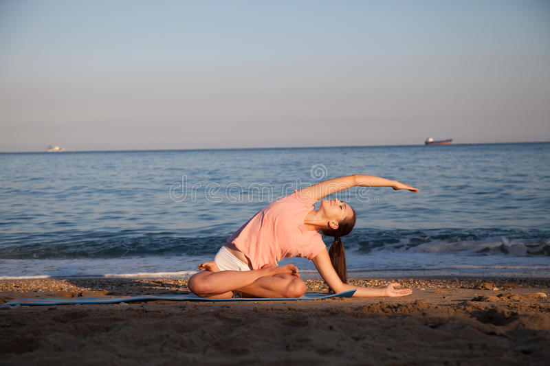 Girl doing gymnastics exercises on the Beach Ocean stock photography