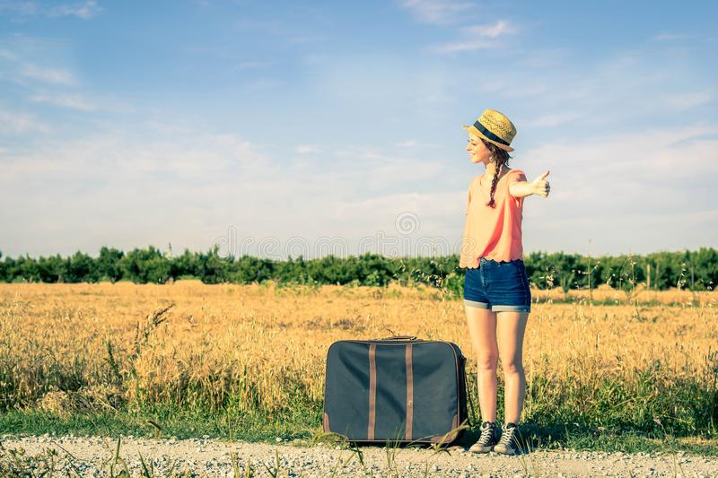Girl doing hitchhiking on the road. Caucasian girl is doing hitchhiking on the road in the countryside stock photos